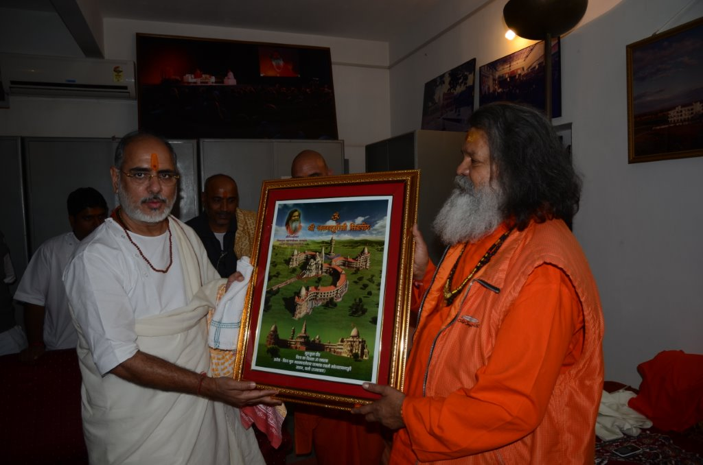 HH Swami Maheshwarananda is giving a foto of Om Ashram to Rameshbhai Ojha